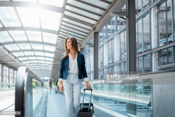 smiling young businesswoman with baggage on moving walkway - travolator stock pictures, royalty-free photos & images