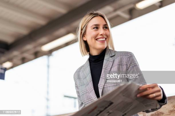 smiling young businesswoman with newspaper at the train station - anzugjacke stock-fotos und bilder