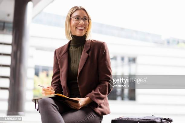 smiling young businesswoman with notebook in the city - pant suit stock pictures, royalty-free photos & images