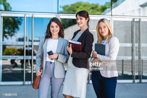 smiling young businesswomen taking classes at university - shoulder bag stock pictures, royalty-free photos & images