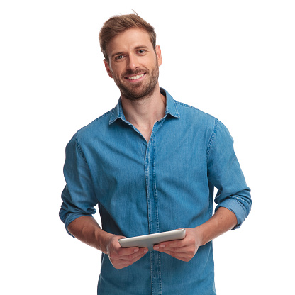 smiling young casual man holding a tablet 1034283778