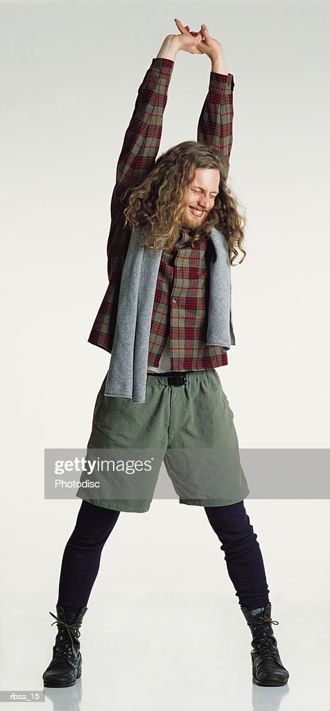 smiling young caucasian adult male hippie with long curly hair wearing a checkered shirt and khaki shorts with a towel over his shoulders stands stretching his arms over his head : Foto de stock