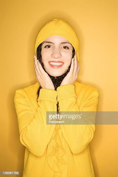 Smiling young Caucasian woman wearing yellow raincoat on yellow background.