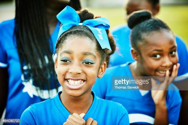 smiling young cheerleader hanging out with teammates after practice - black cheerleaders stock photos and pictures