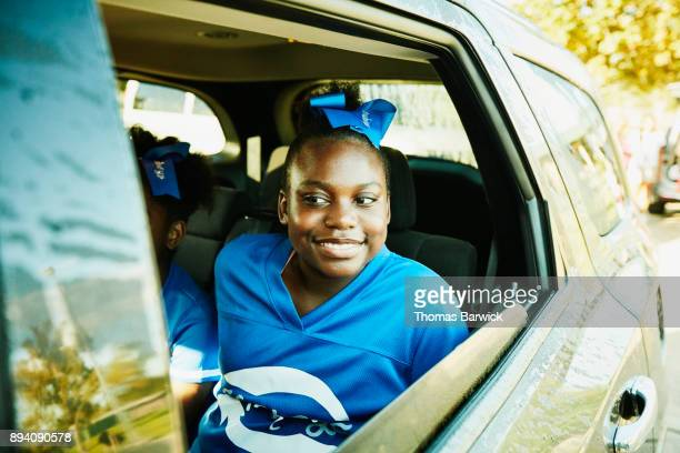 smiling young cheerleader looking out window of car on way to practice - black cheerleaders stock photos and pictures