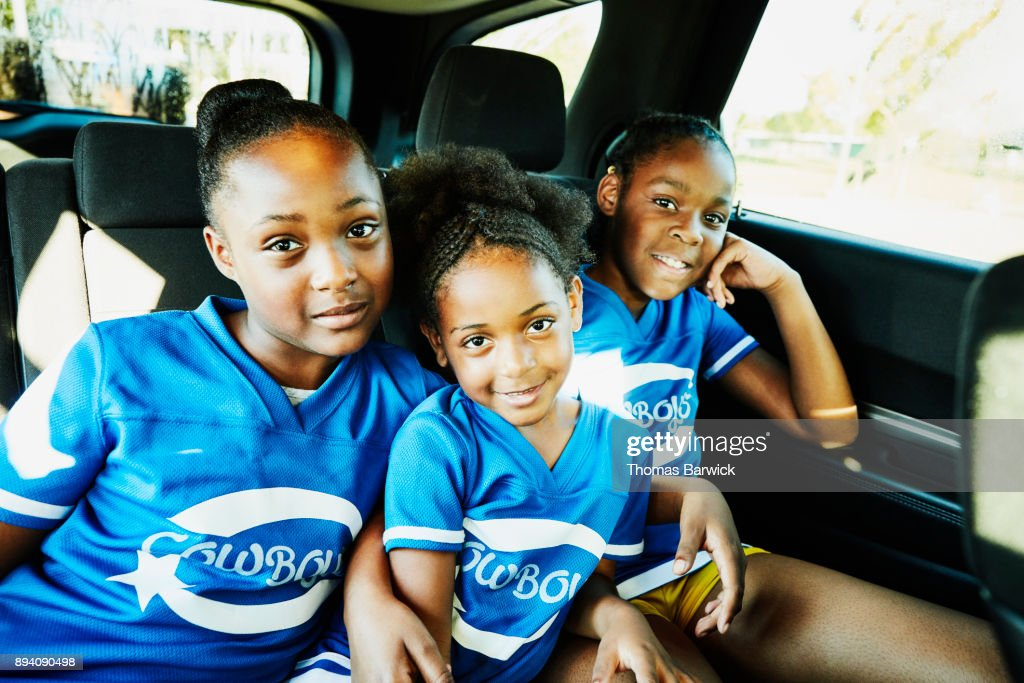 Smiling young cheerleaders sitting in back seat of car on the way to practice : Stock Photo