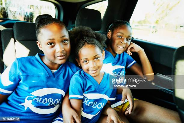 Smiling young cheerleaders sitting in back seat of car on the way to practice
