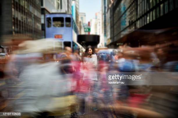 smiling young chinese businesswoman at center of city rush - hong kong stock pictures, royalty-free photos & images