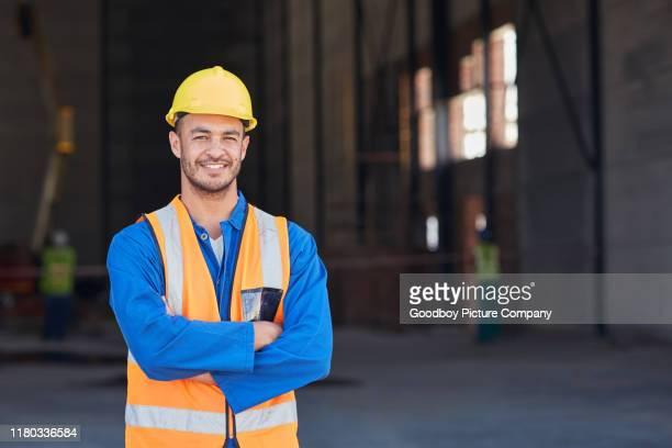 joven trabajador sonriente de la construcción de pie frente a un almacén - ingeniero civil fotografías e imágenes de stock