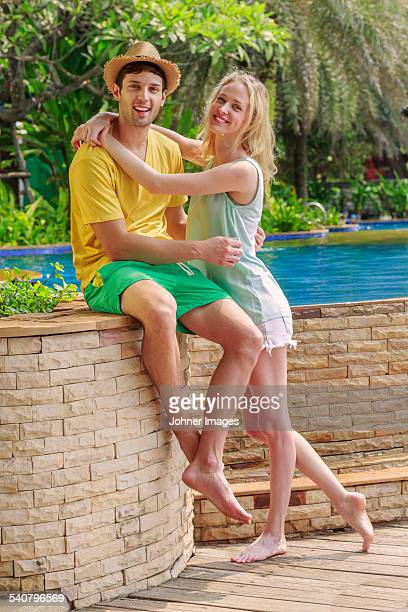 Smiling young couple at swimming pool