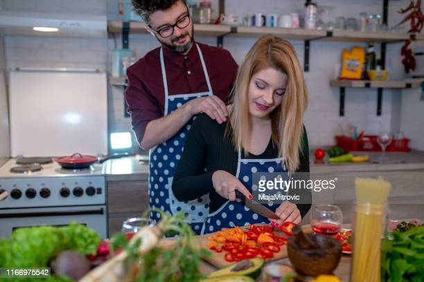 smiling young couple cooking food in the kitchen - kitchenware shop stock pictures, royalty-free photos & images