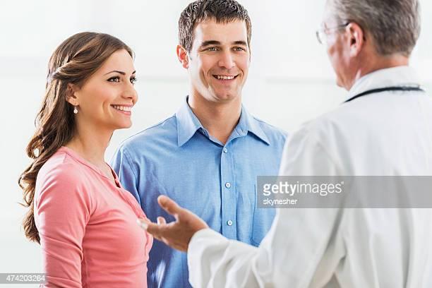 Lächelnd Junges Paar diskutieren mit einem Reifen Arzt.