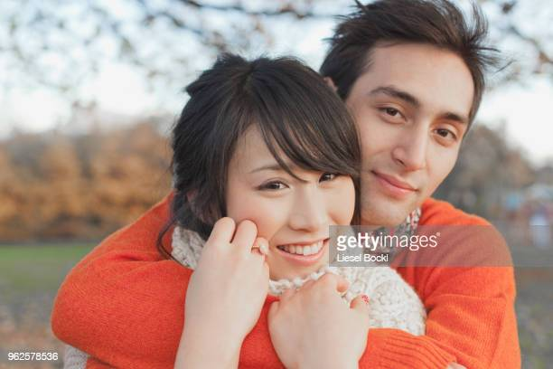 Smiling young couple embracing in park during winter