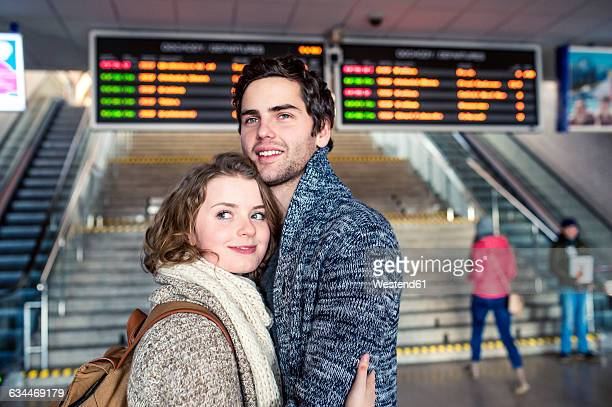Smiling young couple embracing in station concourse