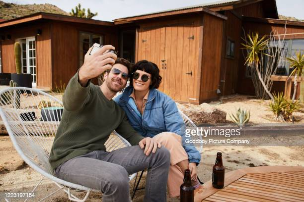 smiling young couple having beers and taking selfies while relaxing outside - beautiful wife pics stock pictures, royalty-free photos & images