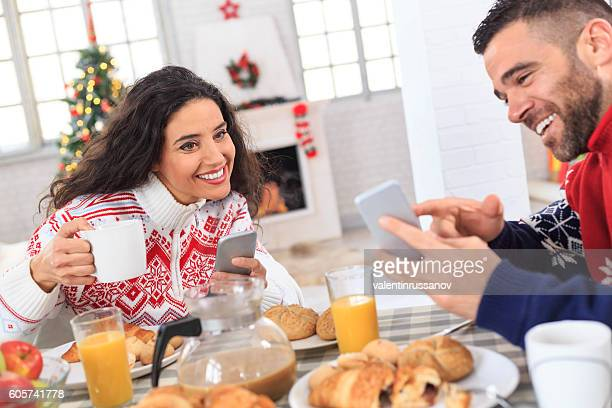 Smiling young couple having christmas breakfast at home