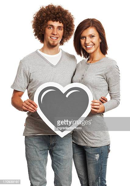 Smiling young couple holding heart sign isolated on white background.