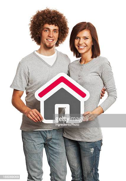 Smiling young couple holding house sign isolated on white background.