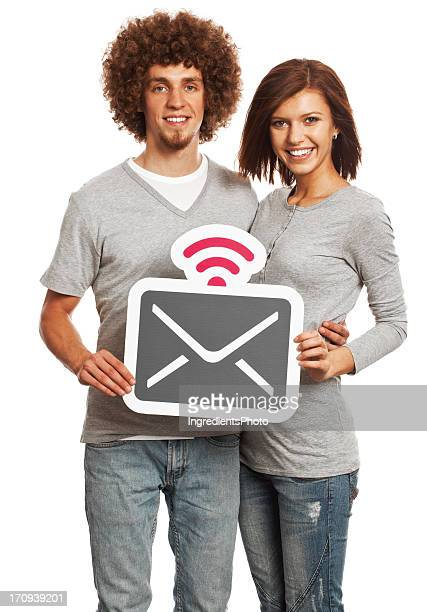 Smiling young couple holding mail sign isolated on white background.