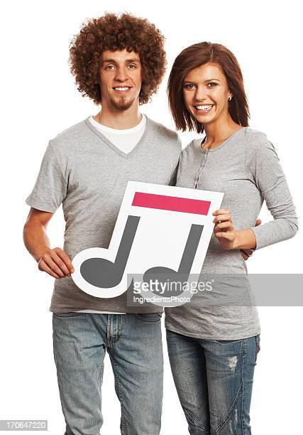 Sonriente joven mestiza sosteniendo música señal aislado sobre fondo blanco.