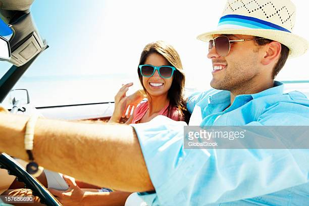 Smiling young couple in a convertible car going for vacation