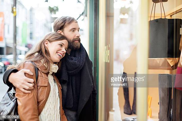 Smiling young couple looking in shop window