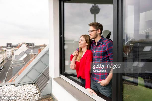Smiling young couple looking out of window in city apartment