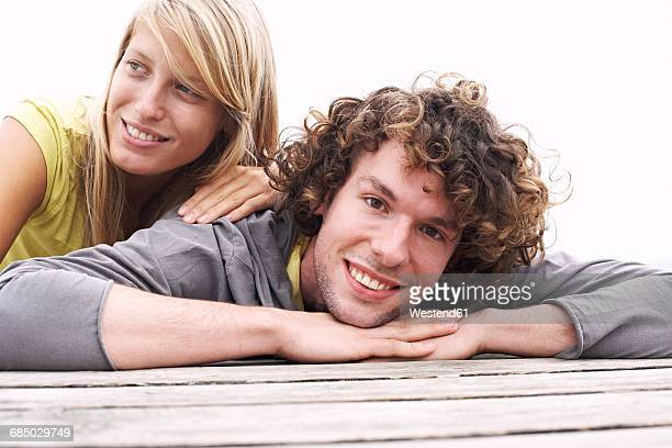Smiling young couple lying on a jetty