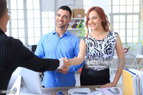 Smiling young couple making a deal with agent