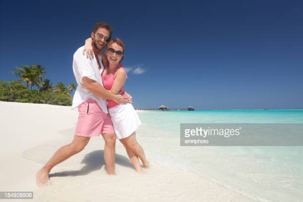smiling young couple on sandy beach