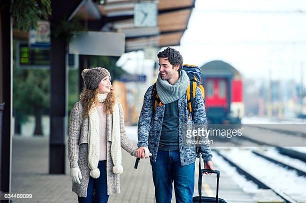 smiling young couple on station platform - bahnreisender stock-fotos und bilder