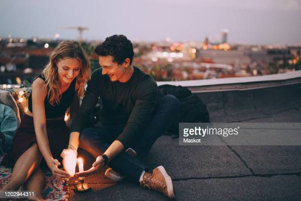 smiling young couple protecting burning candle with hands while sitting on terrace against sky during dusk - junges paar stock-fotos und bilder