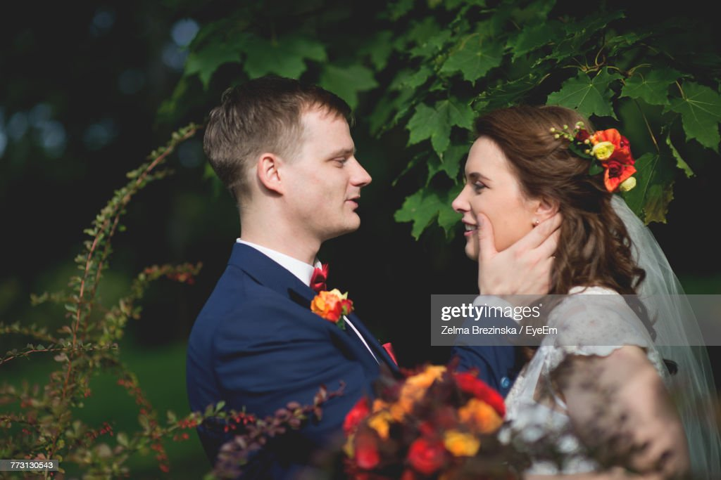 Smiling Young Couple Romancing While Standing At Park : Stock Photo