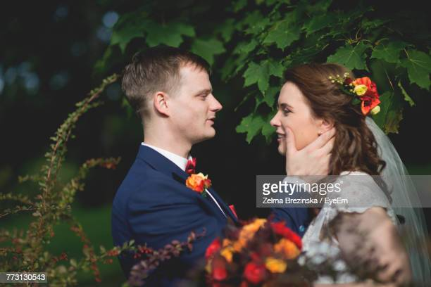 smiling young couple romancing while standing at park - brezinska stock pictures, royalty-free photos & images