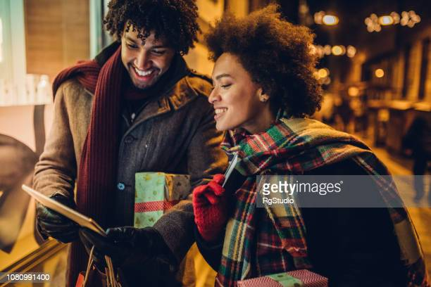 Smiling young couple shopping for Christmas presents online