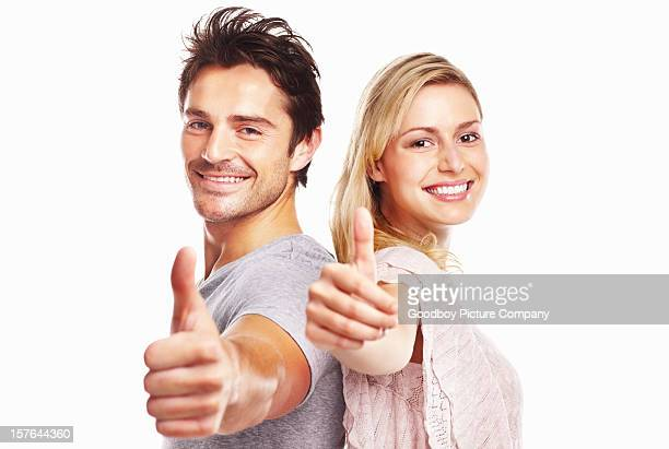 Smiling young couple showing thumbs up sign against white