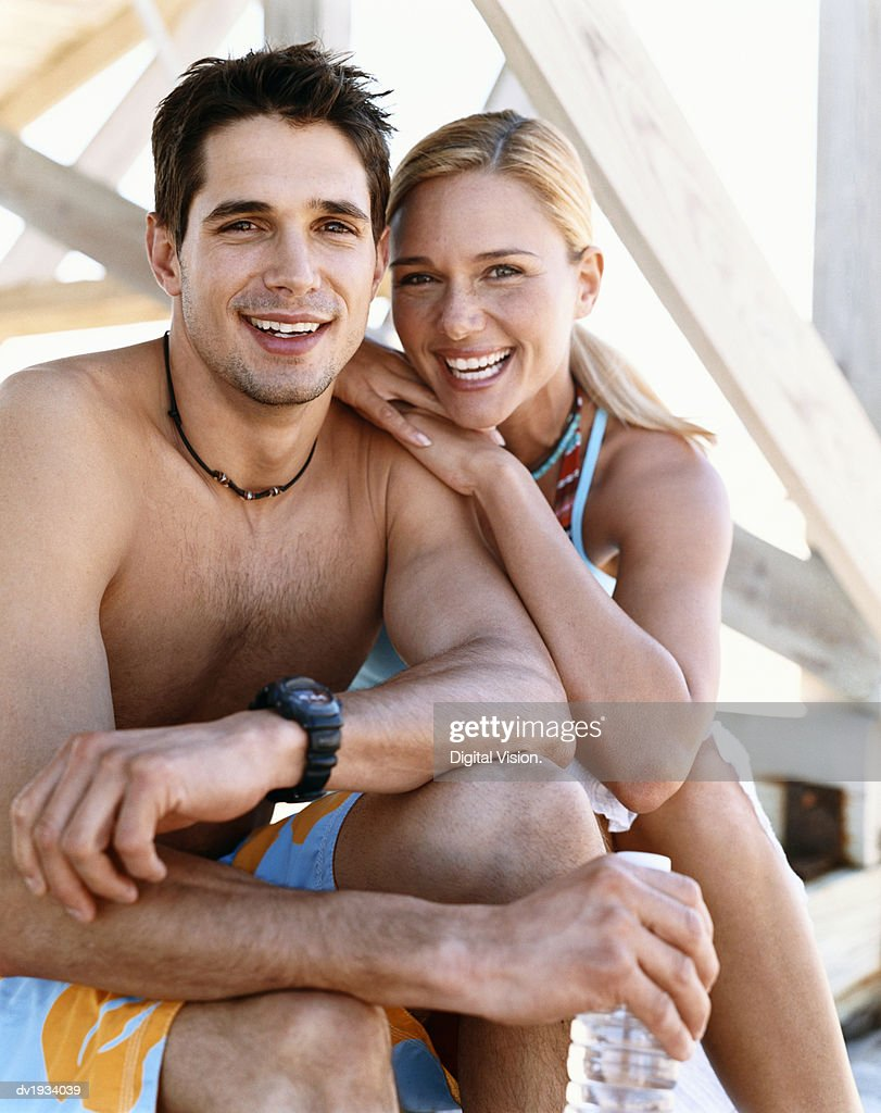 Smiling, Young Couple Sitting Below a Boardwalk : Stock Photo