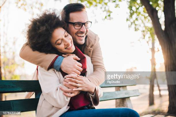 smiling young couple sitting on a bench in the park - valentines african american stock pictures, royalty-free photos & images