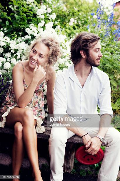 smiling young couple sitting on bench - verlegen stockfoto's en -beelden