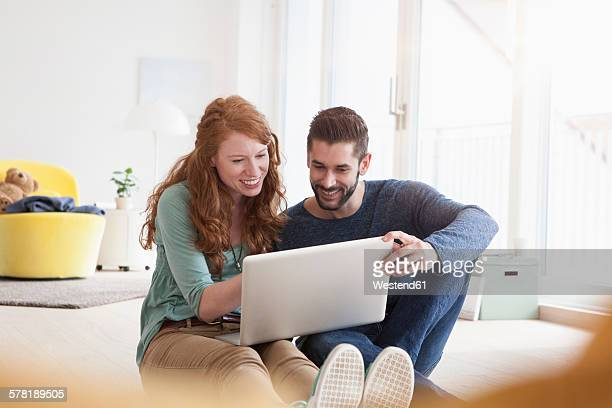 Smiling young couple sitting on floor in the living room using laptop
