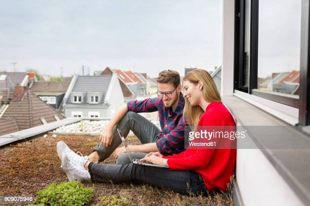 Smiling young couple sitting on roof of city apartment using laptop