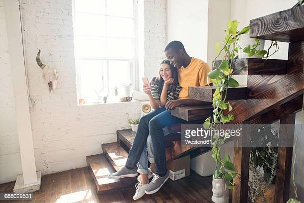 Smiling young couple sitting on stairs in a loft sharing cell phone
