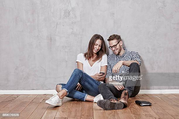 Smiling young couple sitting on the floor with cell phone