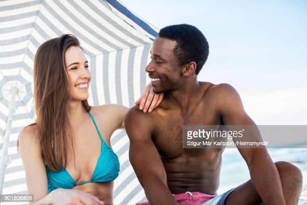 sonriente pareja joven sentado bajo la sombrilla de rayas - chica adulta negra espalda desnuda fotografías e imágenes de stock