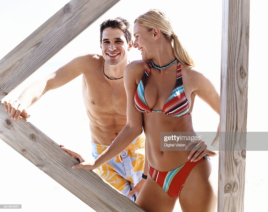 Smiling, Young Couple Standing Below a Boardwalk : Stock Photo