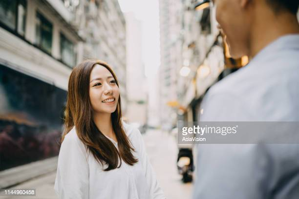 smiling young couple talking on city street in hong kong - first occurrence stock pictures, royalty-free photos & images
