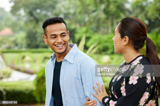 Smiling young couple talking while walking in park