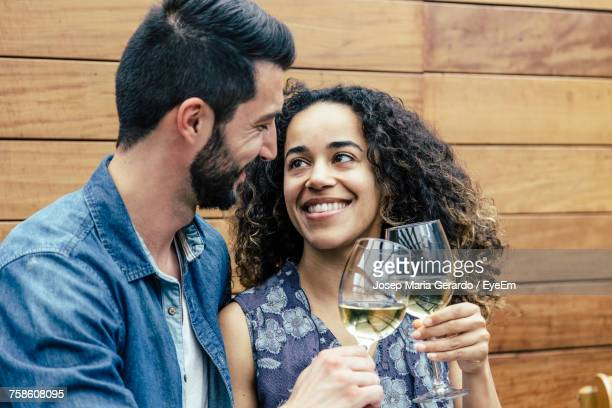 Smiling Young Couple Toasting Wine Against Wooden Wall
