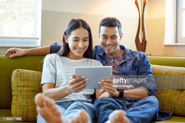 smiling young couple using digital tablet at home - watching stock pictures, royalty-free photos & images