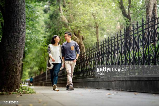 smiling young couple walking on footpath in park - heterosexual couple stock pictures, royalty-free photos & images